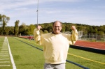 middle age senior man stretching exercising on sports field